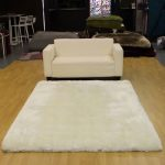 Soft white shaggy area rug with light cream sofa