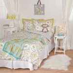 Stylish Bed Shee Design White And Yellow Color On Blanket And Pillows With Fur Rug And Small Tables