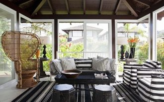Sunroom Interior With Striped Black And White Couches And Rug WIth Pillows And Black TAble