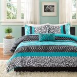 Teal and black bed set with leopard skin pattern white shaggy bedroom rug round bedside table in white a bed furniture with black headboard