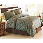 Teal and brown bedding idea with teal and brown pillows a bed frame with curly headboard a bedside table with decorative vase and flowers