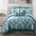 Teal bedding with beautiful pattern and teal pillows a bed furniture with white headboard white wooden bedside table with storage  white shag bedroom rug