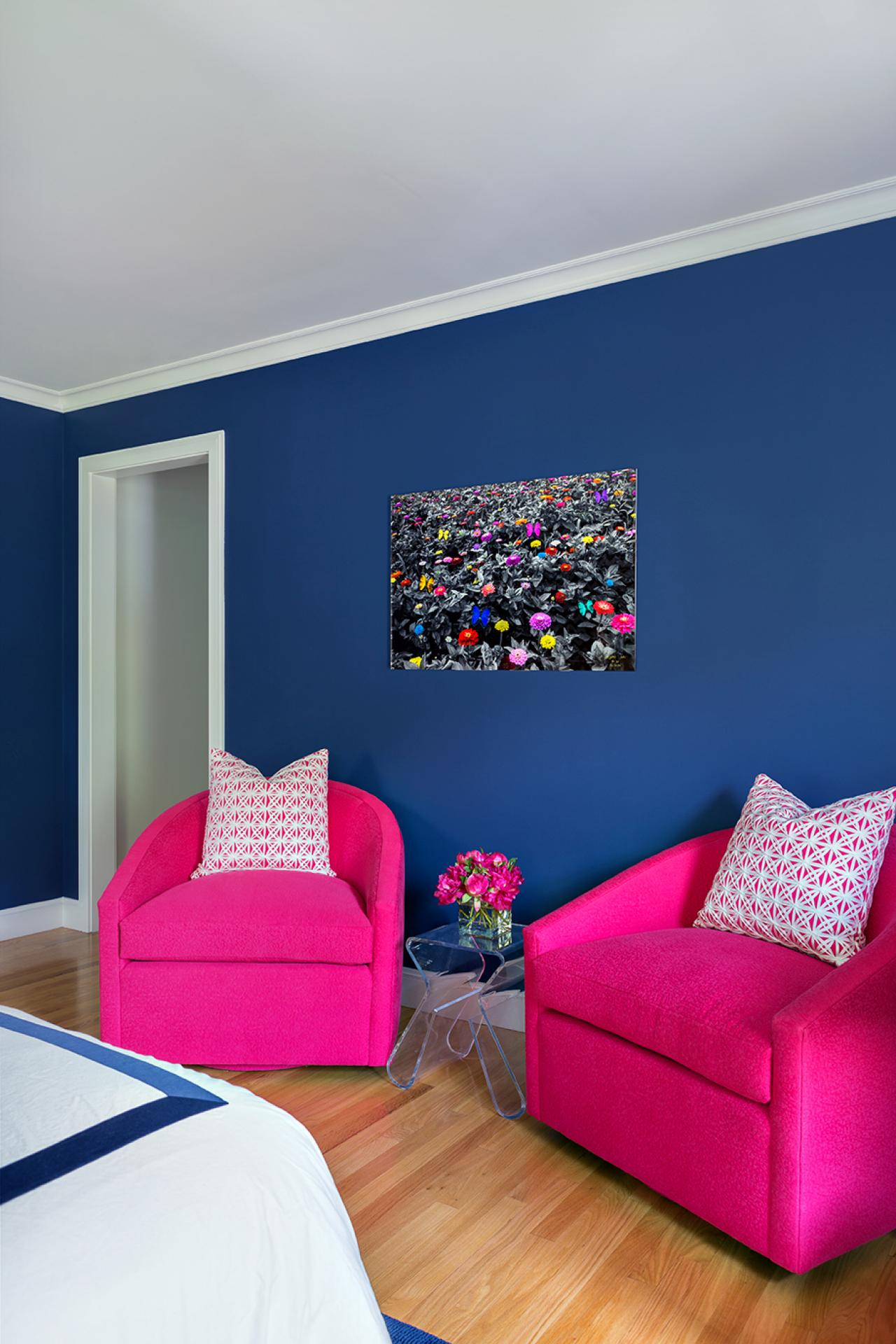 teen bedroom with two pink chairs and blue wall painting and white bed