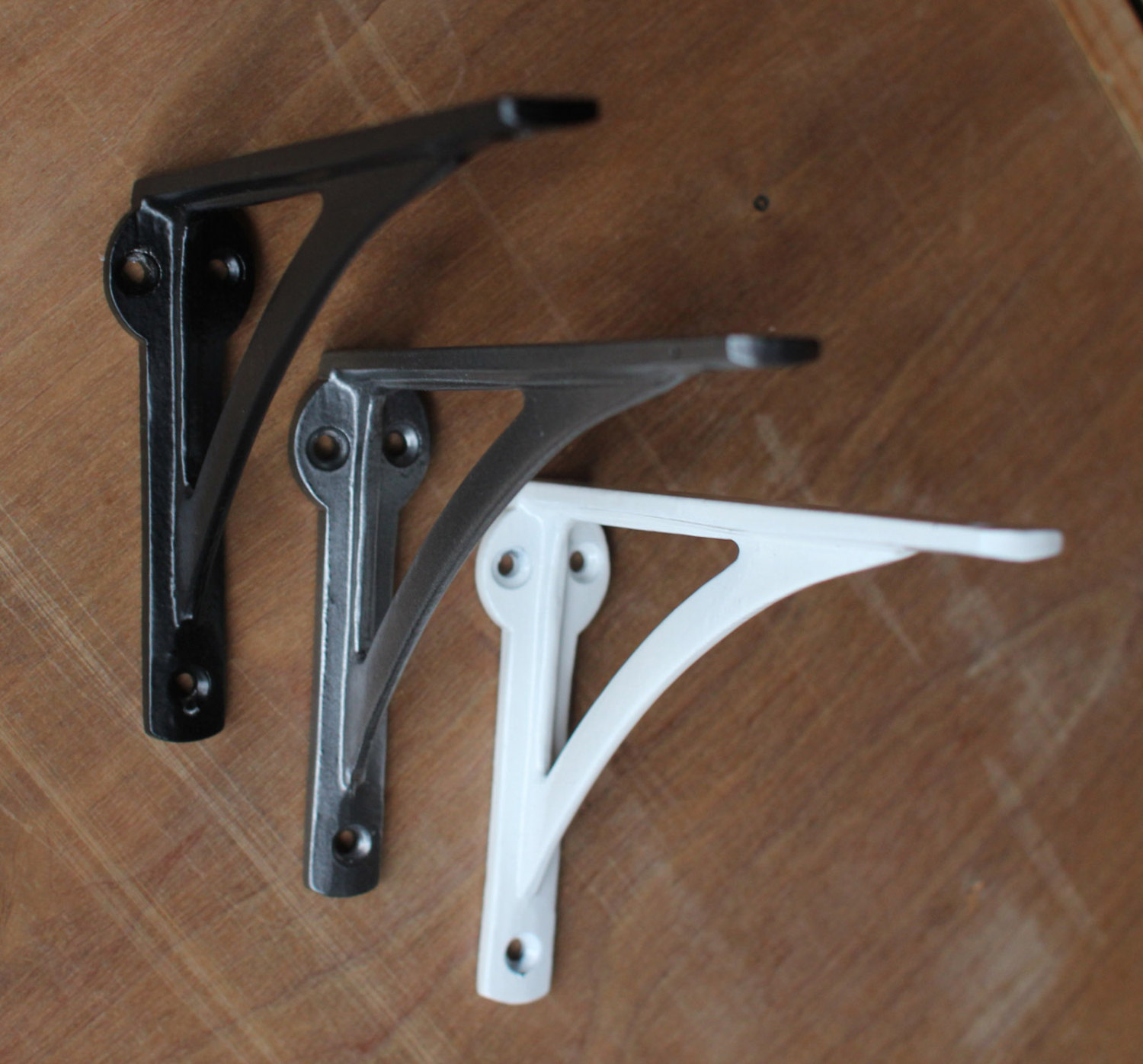 three colors of metal shelf brackets