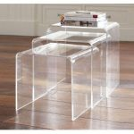 Three clear acrylic nesting side tables with a pile of books