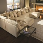 U Shaped Sectional Chaise With Pillows Glass Table And Striped Rug