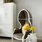 Unique French styled chair for reading with yellow throw pillow a white clothes closet organizer a decorative side table in white paint