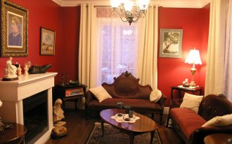 Victorian Living Room With Red Wall White Curtains Brown Sofa Wooden Table Stylish Rug And White Fireplace