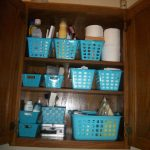 Wall bathroom cabine t with blue plastic storage boxes
