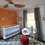White Baby Crib In Grey And Orange Wall WIth Decorative Carpet White Chair And Small Table Decorated By Fan And Grey Curtains