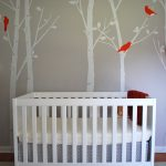 White Baby Crib With Pretty Wallpaper And Grey Carpet On Floor