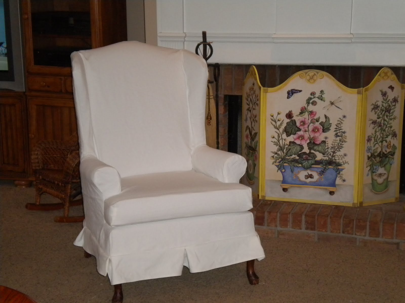 White Chair Slipcover Near Fireplace With Flower Cover