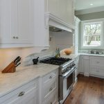 White Kitchen WIth Stove And Hardwood Floor