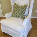 White Slipcovered Chair With Green Pillow