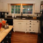 White painted base and wall cabinet clearance  with black stained metal handle feature glossy black kitchen counter idea