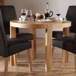 Wood round dining table for four black leather seaters