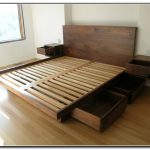 Wooden king platform bed frame with drawers underneath and headboard plus mounted bedside tables