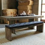 Wooden kitchen table with black upholstered bench in rustic style
