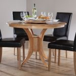 Wooden round dining table with four black leather dining chairs