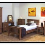 a bedroom NYC consisting of a single bed furniture with  headboard and footboard a pair of cabinet systems a side table with table lamp a wooden vanity with mirror and backless seat unit a closet