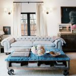 a-factory-cart-rustic-coffee-table-with-wheels-with-blue-cover-and-flowers-centerpiece-and-sofa-and-picture-on-white-wall-and-wall-lamps-and-white-table-lamp