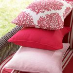 a pile of throw pillows for outdoor furniture sets which consists of light pink pillow deep pink pillow and pink plus white floral patterned pillow