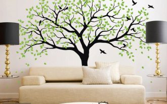 adorabke temporary wall covering idea with green black tree pattern above the elegant creamy sofa design with round cofffee table and black floor lamps and patterned area rug