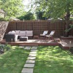 Adorable Backyard Patio Design Idea With Lattice Wooden Fence And Wooden Stage Flooring And Walkway And White Sofa And Rectangle Coffee Table And Grassy Meadow