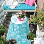 adorable balcony idea with wooden fence and blue tufted bolster on white bench with turquoise area rug and round coffee table and garden
