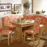 adorable coral colored corner dining table set with chairs and banquette and creamy area rug and wall pictures and centerpiece