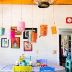 adorable dining room with colorful chairs in blue and yellow with colorful pendant lamps beneath wooden ceiling
