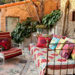 adorable retro garden furniture idea with metal chair with colorful throw and cushions and red chair