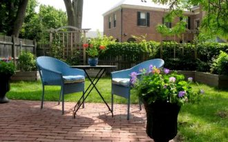 adorable super green backyard patio design with garden and paved flooring and potted plants and best blue seating with black metal coffee table