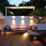 awesome backyard patio design with wooden deck and gray modern bench with colorful stripe cushions and modern lighting and white siding