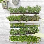 beautiful vertical garden and home catalog with hanging plants and white brick siding and white chair and wooden floor