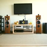 beige tone ikea stereo cabinet design beneath tv set on white wall with black metal storage