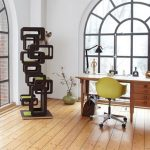 Black Retro Cat Tree By Wohnlock Near Wooden Desk And Big Glass Windows On White Wall And Wooden Floor And Yellow Chair And Flowers In Green Vase And Black Table Lamp