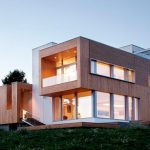block model energy efficient home design with open concept and bright light and beige wooden siding
