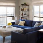 blue navy L shaped sectional furniture with armrest and some decorative pillows large upholstered ottoman table