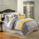 bold yellow and gray bedroom decor with wooden headboard and bronze table lamp and gray wall paint