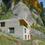 boxy modern home design on hillside idea with yellow tone with concrete siding and glass window and lush vegetation