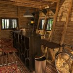 brown furniture-and-maroon-chairs-inside-pentagon-cabin-plans-also-brown-trash-can-beside-bycicle-and-pendant-brown-lamp