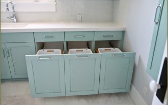 built-in-and-hidden-laundry-hamper-inside-cabinet-near-sink-with-three-white-hampers-in-the-corner-near-white-wall