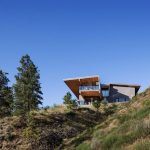 challenging design of modern home on hillside with open plan with grassy ground with trees