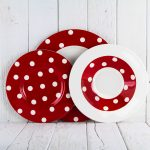 cheerful red and white polka dot dishes design for  fun christmas event of plates on wooden deck