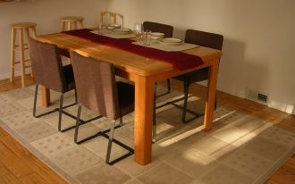 classic dining space with creamy rug and wooden table with centerpiece and brown upholstered chairs
