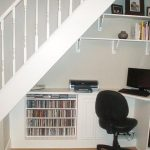 classic white understairs home office idea with white desk and white wall racks and black swivel chair and white stairs