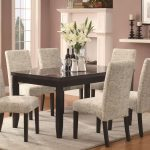 classic white upholstered dining chair design on white rug with wooden table with glass window and orchid