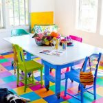 colorful playroom design with rainbow tile flooring and white blue table and yellow chairs and pink
