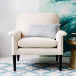 comfortable-anders-armchair-with-white-color-and-grey-cushion-near-small-wooden-table-and-large-tosca-picture-on-white-wall-and-a-carpet-on-the-white-ceramic-floor